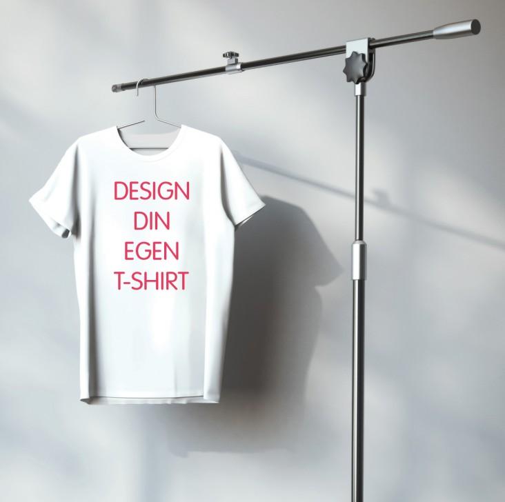 Design din egen T-shirt. Dekorations billede - T-shirt hænger på et stativ med teksten: Design din egen t-shirt