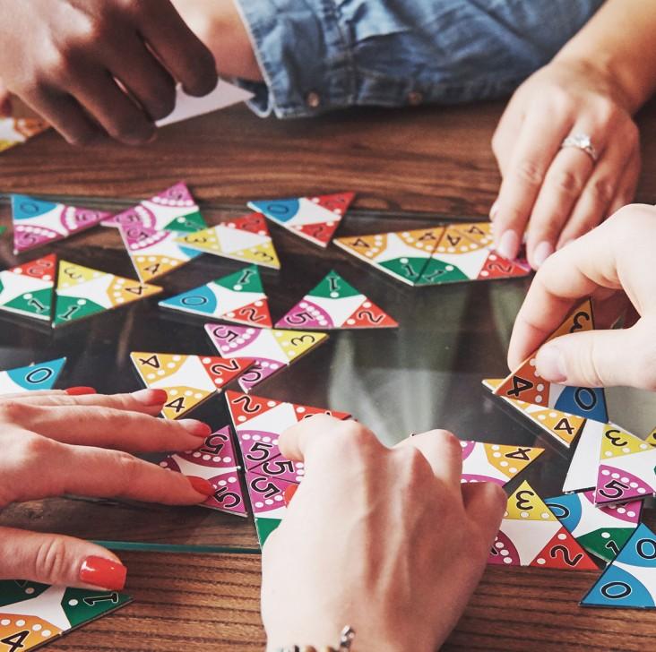 Brætspil. Dekorationsbillede - elever sidder ved et bord og spiller brætspil
